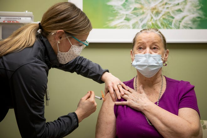 Kim Arvin, a pharmacist, administers the first dose of Moderna's COVID-19 vaccine to Connie Fullerton, of Delhi, at Good Samaritan-Western Ridge in Green Township on Thursday, January 21, 2021.