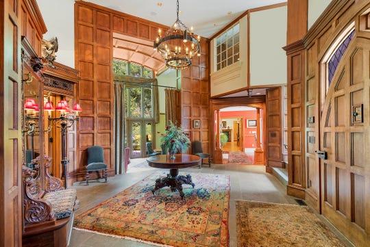 Un mur de panneaux de deux étages autour des portes en verre s'élève dans un jardin dans cette maison unique en son genre à Barton Hills.  La maison est conçue autour d'une abondance de chefs-d'œuvre architecturaux et de travaux originaux d'artisans.