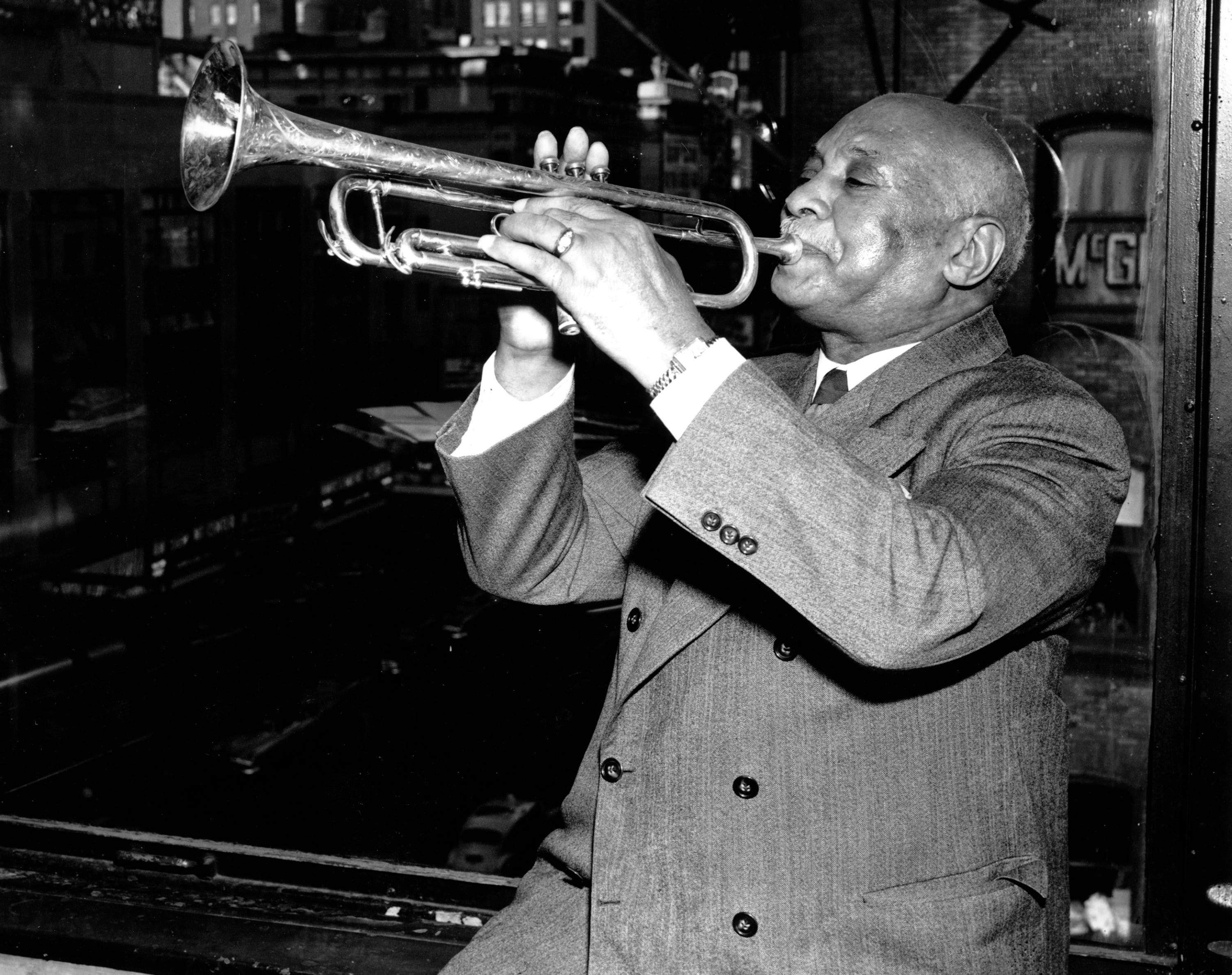 """W.C. Handy, father of """"the St. Louis Blues,"""" sits in front of a window overlooking Times Square as he plays his trumpet in his New York publishing office on Nov. 11, 1949."""