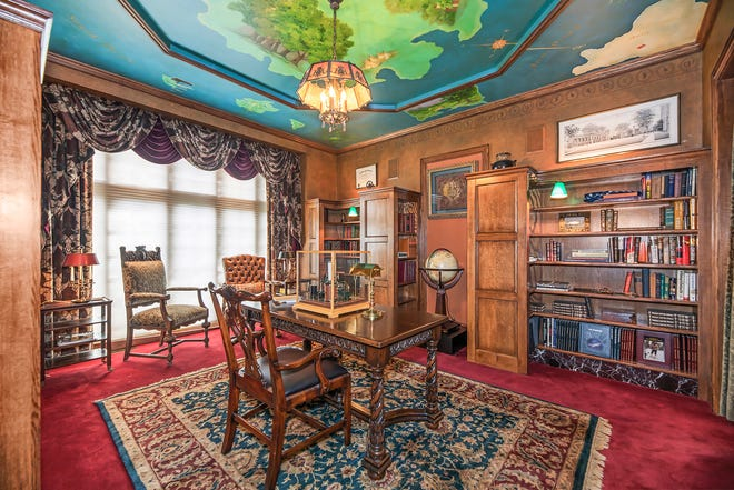 La bibliothèque avec une peinture de l'artiste Neverland au plafond de la maison au 264 Barton Shore Dr. à Ann Arbor.  Cette maison unique et créative regorge d'antiquités architecturales et de nouvelles œuvres d'artisans.