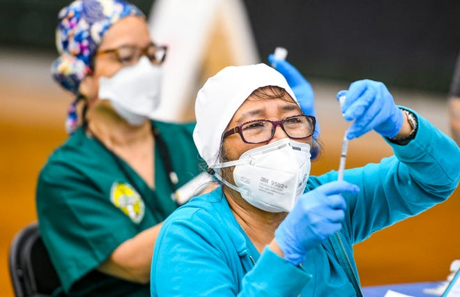 Department of Public Health and Social Services Nurse Eva Losbanes carefully withdraws an exact measured dose of the Pfizer-BioNTech COVID-19 vaccine at a vaccination clinic at the UOG Calvo Field House in this Jan. 21 file photo.