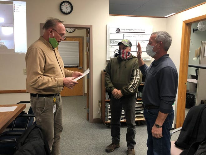 Richland County Commissioner Cliff Mears, left, swore in Robert McConkie, Jr., center, and Brian Alt to the SWCD Board of Supervisors on Tuesday.