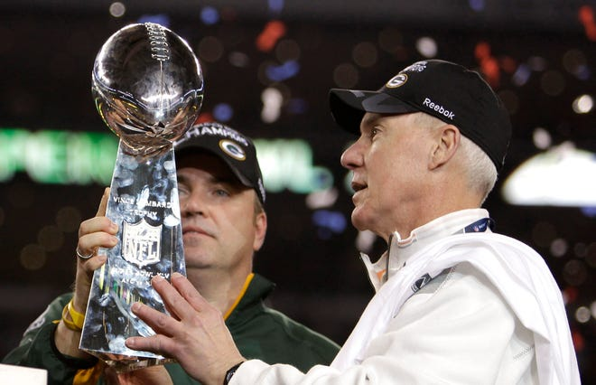Green Bay Packers coach Mike McCarthy, left, and General Manager Ted Thompson look at the Vince Lombardi trophy after the Packers beat the Pittsburgh Steelers, 31-25, in Super Bowl XLV on Feb. 6, 2011, in Arlington, Texas.