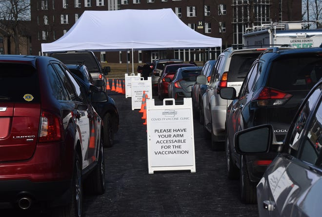A line of cars waits their turn during the Licking County Health Department's first drive in COVID-19 vaccine clinic on Thursday, Jan. 21, 2021 on the campus of the Ohio State University in Newark. The clinic was open to those 80 years old and older, in keeping the the state's Phase 1B distribution plan for the vaccine.
