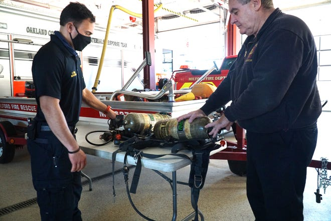 Milford Fire Chief Tom Moore, right, and firefighter Chad Scime take a look at some breathing apparatus at Fire Station #1.