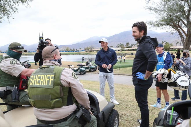 Jake Owen, right, and Paul Casey chat with Mike Scott and Arnold Iniguez with the Riverside County Sheriff's Department after Owen struck Scott with a golf ball that landed during the American Express Charity Challenge at PGA West in La Quinta, January 20, 2021. Scott was unhurt.