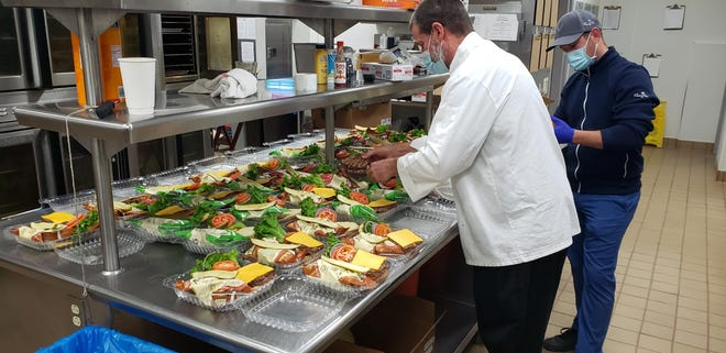 Classic Club Executive Chef Gerard Brunett works with Assistant General Manager Ruan Krugel packaging burgers to donate to the Coachella Valley Rescue Mission.