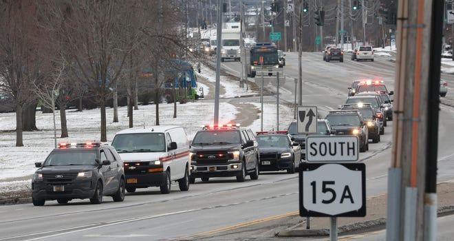 Law enforcement personnel escort the bodies of National Guardsmen to the Monroe County Medical Examiner's Office in Brighton, N.Y., on Jan. 21.  Three Guard members were killed when their helicopter crashed on a training flight in Mendon the night before.