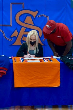 Central High School student Hailey Smith signing with Trinity Valley Community College with head cheer coach Vontae Johnson.