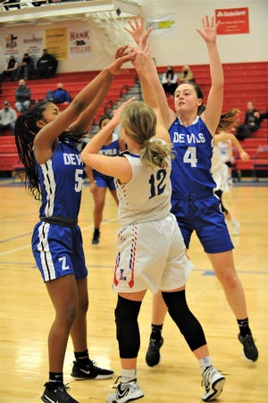 Lakewood's Camryn Martindale passes over Zanesville's Emmah Kronenbitter (4) and Chiara Black (5) during Wednesday's Licking County League contest. The Lady Devils won 44-36.