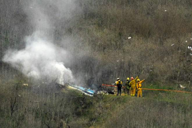 Firefighters work the scene of a helicopter crash where former NBA star Kobe Bryant died in Calabasas, Calif., on Jan. 26, 2020. Bryant is the game's fourth-leading scorer. He spent 20 years with the Los Angeles Lakers, 18 as an All-Star, and won five titles. Then came the helicopter crash in the fog-shrouded California hills that reverberated across sports and across continents.