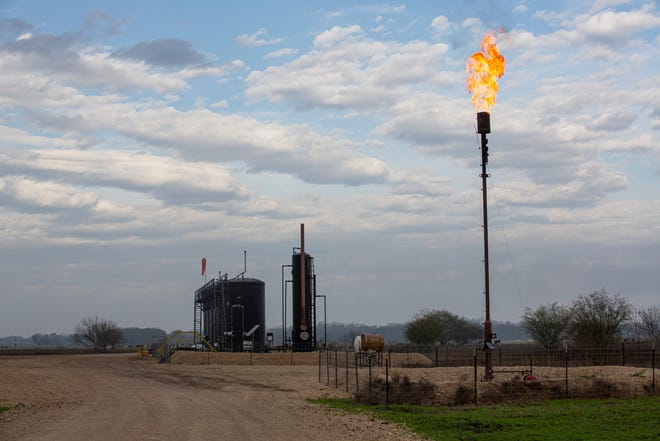 A natural gas flare is seen near a drilling operation near Gonzales, Texas on Friday, Jan. 22, 2021.