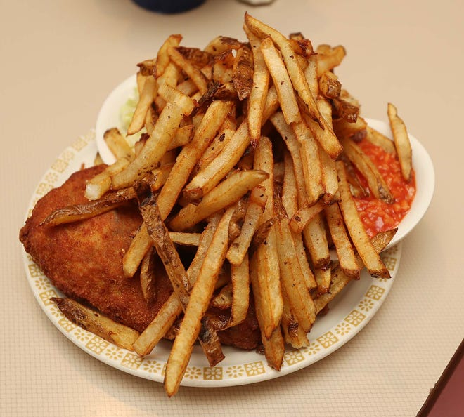 The signature chicken dinner served with a mound of fresh cut french fries, hot sauce and cole slaw at Village Inn Chicken in Norton.