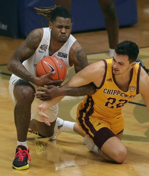 University of Akron's Bryan Trimble Jr. and Central Michigan's Matt Beachler scramble after a first-half loose ball on Thursday, Jan. 21, 2021, in Akron, Ohio, at Rhodes Arena. [Phil Masturzo/ Beacon Journal]