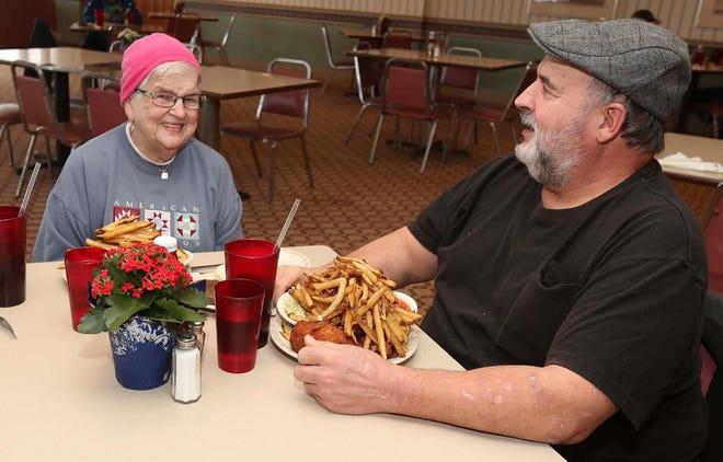 Josette Momchilov, left, and her son Gipp Momchilov of Wooster enjoy their chicken dinner at Village Inn Chicken in Norton.