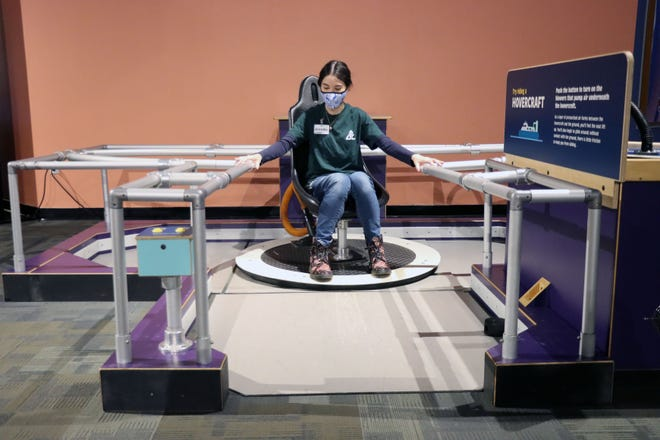 Jennifer McClellan demonstrates the Hovercraft which is part of the Don Harrington Discovery Center's new exhibit From Here to There which explores the science of how things move. [Neil Starkey / For the Amarillo Globe-News]