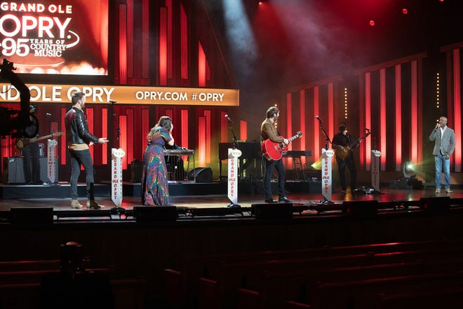 """Lady A members Charles Kelley, Hillary Scott and Dave Haywood respond to their Grand Ole Opry membership invitation by Opry member Darius Rucker on Jan. 21. The segment was recorded during taping for the NBC special """"Grand Ole Opry: 95 Years of Country Music"""" to air Feb. 14."""