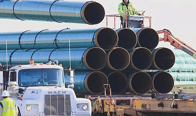 Workers unload pipe in South Dakota in 2015 as construction continued on the Dakota Access pipeline. On Thursday, the acting Secretary of Interior issued a suspension of any ongoing work the agency was doing to permit future energy recovery activities from federal reserves, both on- and off-shore.
