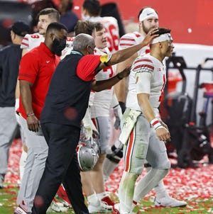 Ohio State athletic director Gene Smith, left, consoles quarterback Justin Fields after the Buckeyes' loss to Alabama in the College Football Playoff national championship game on Jan. 11 in Miami Gardens, Fla.