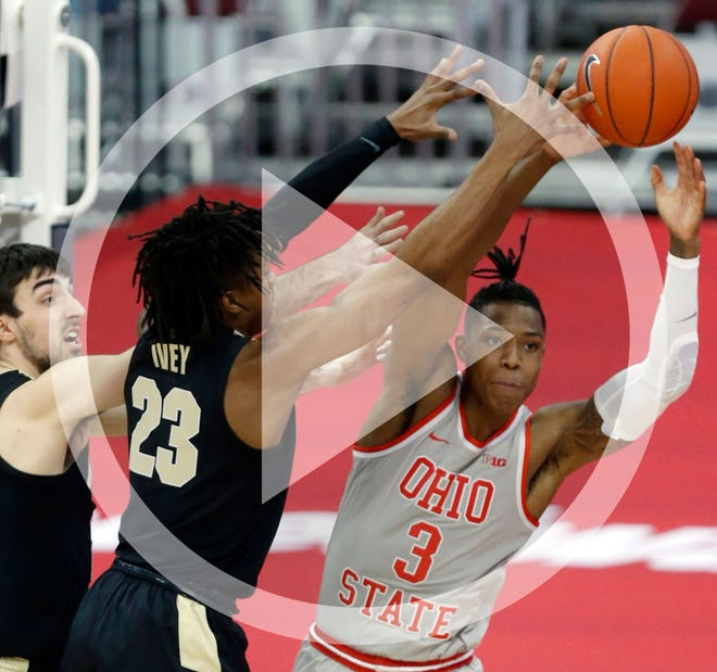 Ohio State guard Eugene Brown, right, passes against Purdue guard Ethan Morton, left, and guard Jaden Ivey during the first half of an NCAA college basketball game in Columbus, Ohio, Tuesday, Jan. 19, 2021.