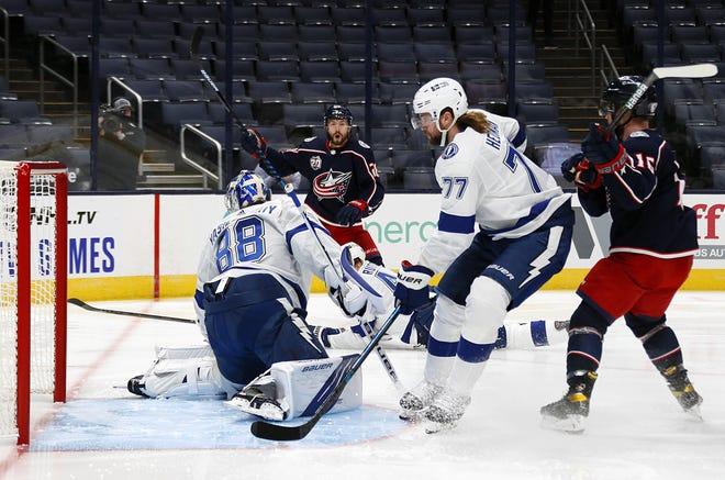 Oliver Bjorkstrand (28) scores a goal 21 second into a game Thursday against Tampa Bay Lightning goaltender Andrei Vasilevskiy (88). Bjorkstrand added an assist, but the Blue Jackets lost 3-2 in overtime.