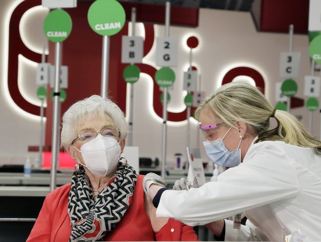 Dr. Kelli Barnes gives a dose of the COVID-19 vaccine to 100-year-old Helen Formet during the first day of inoculations of seniors age 80 and more on Tuesday at Ohio State University's Schottenstein Center in Columbus.