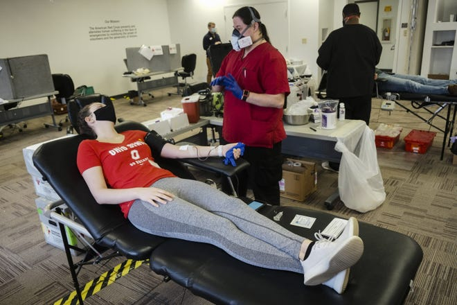 Olivia Howard, left, of Columbus, leans back as Travis McPherson, a specialist with the American Red Cross, chats with her after starting her blood donation on Friday. By giving blood, some donors are able to get quick insights to their health.