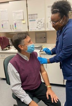Dr. Chip Riggins, regional administrator of the Louisiana Department of Health, receives his coronavirus vaccine.