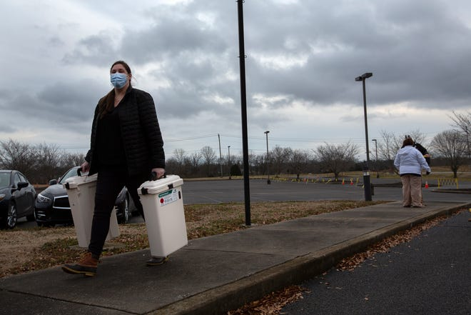 Maury Regional Health Group's Jessica Brown carries two containers of used syringes at a drive-thru distribution center for the COVID-19 vaccine at  Columbia State Community College in Columbia, Tenn., on Thursday, Jan. 21, 2020.