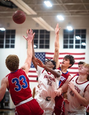 Van Horn's Brycen Dean (12) drives into Bishop Miege traffic for a shot in Thursday's game at Van Horn. Dean scored 28 points but the Falcons lost 70-59.