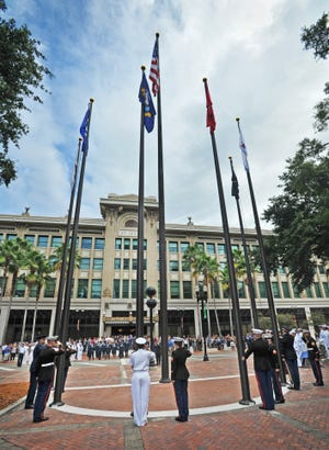 Military personnel raise flags of the five branches of service as well as the POW/MIA flag outside Jacksonville City Hall in the 2018 photo.