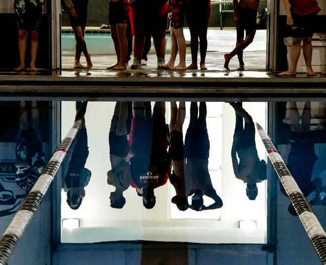 A group of competitors and coaches are reflected in the Garden City Family YMCA pool as they wait in a doorway for a Garden City High School boys swim meet to begin on Thursday.