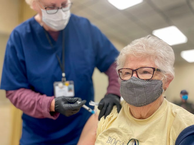Carol Lindstrom of Galesburg, right, receives a COVID-19 vaccination injection from Penny Bolliver R.N. during the second day of the Knox County Unified Command's vaccine clinic at the Knox Co. Farm Bureau on Jan. 22, 2021.