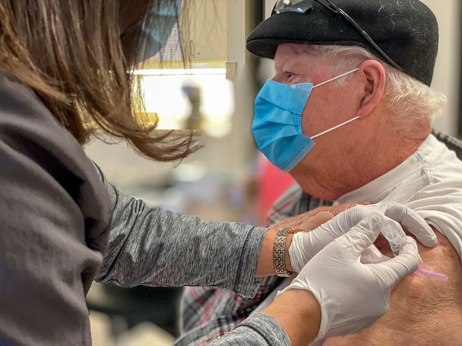 Robert Brand, 88, of Galesburg receives a COVID-19 vaccine injection from Trish Johnson R.N. at the OSF St. Mary Medical Group building on Friday, Jan. 22, 2021. OSF offered vaccinations to a select group of their patients who are over the age of 65, via appointment only.