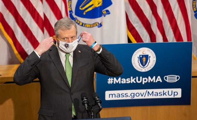 Massachusetts Gov. Charlie Baker puts on a face mask emblazoned with the state seal.