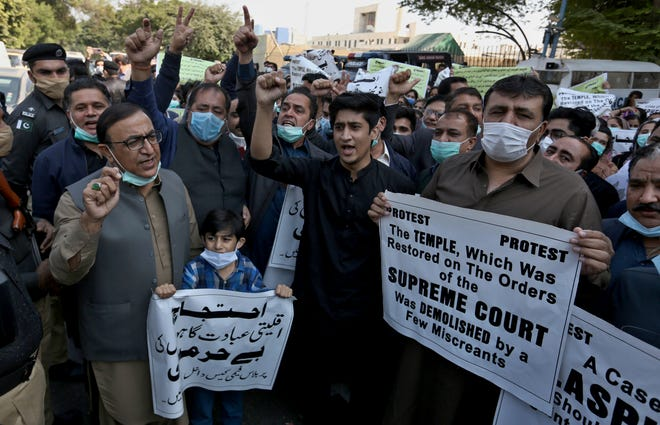 Members of Pakistan Hindu Council hold a protest against the attack on a Hindu temple in the northwestern town of Karak, in Karachi, Pakistan, on Dec. 31, 2020. Pakistani police arrested 14 people in overnight raids after a Hindu temple was set on fire and demolished by a mob led by supporters of a radical Islamist party, officials said.
