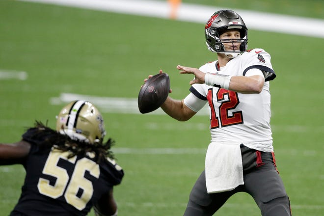 Tampa Bay Buccaneers quarterback Tom Brady (12) passes in front of New Orleans Saints outside linebacker Demario Davis (56) during the second half of an NFL divisional round playoff football game, Sunday, Jan. 17, 2021, in New Orleans.