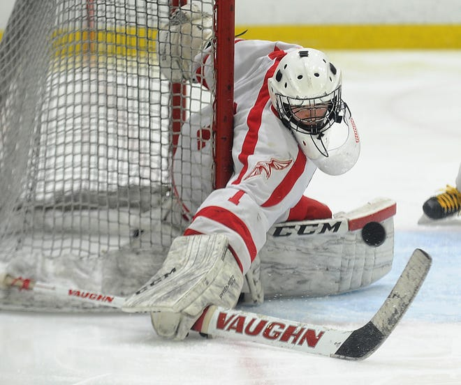 Hudson goalie Kyle Gonzalez pushes aside a shot  during a game against Marlborough at Warrior Ice Arena in Boston last season. Junior Paul Melo is taking over goaltending duties this season after Gonzalez graduated last spring.