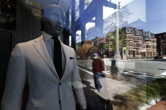 A man walks past a storefront window in Boston. The state reported Friday that its jobless rate rose from 6.7% in November to 7.4% last month.