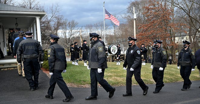 Members of the Wayland Police Department enter the John C. Bryant Funeral Home in Wayland to pay their respects at the wake of Wayland police officer Chris Cohen, Jan. 22, 2021. More than 200 law enforcement personnel from surrounding communities attended the wake. Earlier, a community caravan of more than 100 cars passed by as members of the Cohen family watched from the porch of the funeral home. Cohen, a member of the Wayland Police Department since 1996, died unexpectedly Jan. 17 in his Framingham home. He was 51.
