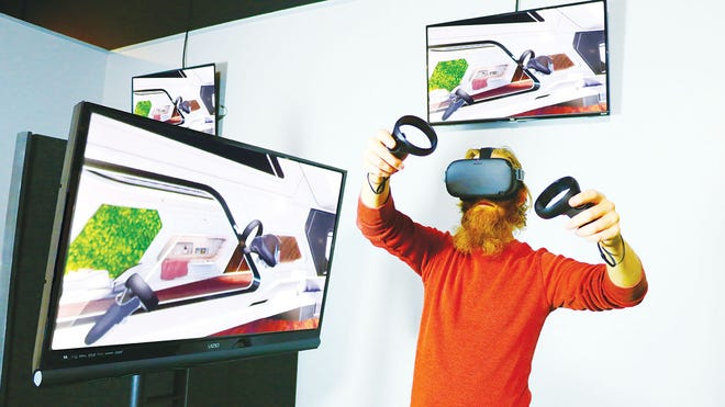 Quinn Argall, the American Museum of Science and Energy's new curator, is developing a virtual reality gallery. Here he is wearing a VR headset and holding sensors that allow him to interact with a computer-generated simulation of a three-dimensional image or environment.