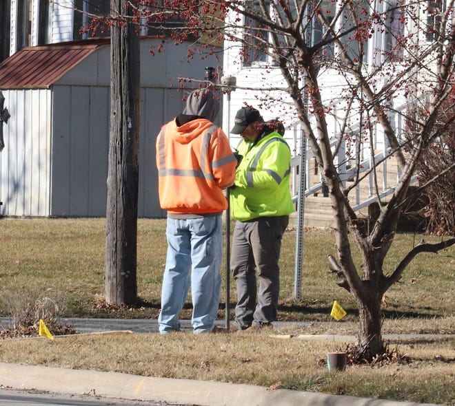 two surveyors go over their numbers and notes while doing their job at the corner of Water and Hazel streets in Pontiac.