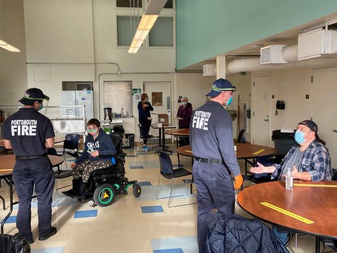 Portsmouth Fire Department members help Cross Roads House residents test for the coronavirus.