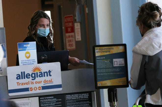 Passengers get their boarding passes checked as they leave the newly remodeled airport terminal to get on an Allegiant flight to Florida from Portsmouth International Airport at Pease Friday, Jan. 22, 2021.