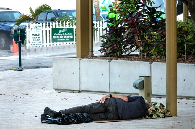 A man sleeps by the Great Lawn and Lake Pavilion in downtown West Palm Beach.
