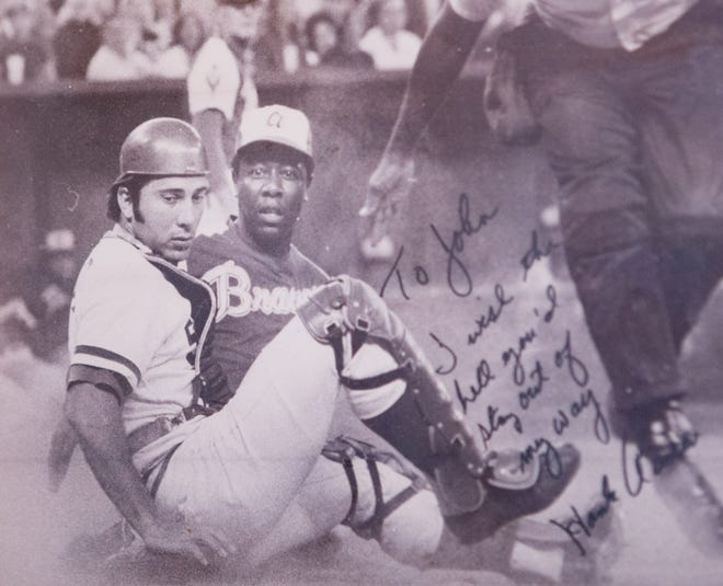 A photo of Cincinnati Reds great Johnny Bench making a play at the plate against fellow hall of famer Hank Aaron is displayed in the trophy room of Bench's Palm Beach Gardens home.