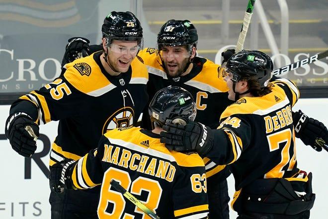 Boston Bruins defenseman Brandon Carlo (25) celebrates his goal with teammates Patrice Bergeron (37), Jake DeBrusk (74), and Brad Marchand (63) in the third period against the Philadelphia Flyers, Thursday.