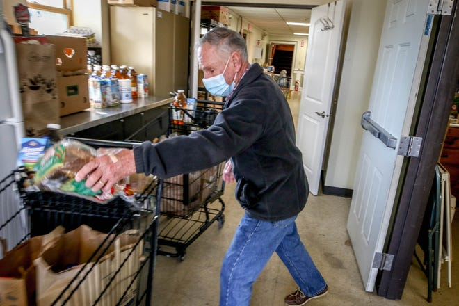 Paul St. Laurent adds a loaf of bread to a carriage filled with items for distributon at a food pantry operated by St. John's Masonic Lodge in Portsmouth.