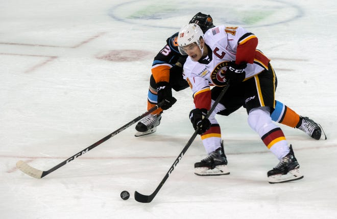 The Stockton Heat's Byron Froese, right, fights for the puck with San Diego Gull's Patrick Sieloff during the Heat's AHL home opener Oct. 12, 2019, at Stockton Arena in downtown Stockton.