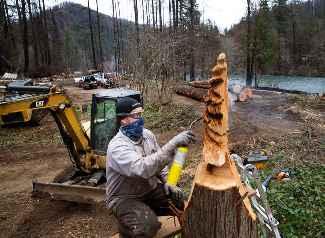Chainsaw artist Jay Peppard creates a sculpture from one of the stumps left behind as he and a crew from ALLGTMH LLC work to clear a piece of property burned over by the Holiday Farm Fire. The crew has cleared and done construction on more than 30 properties as homeowners turn their attention toward rebuilding along the Mckenzie River Valley.